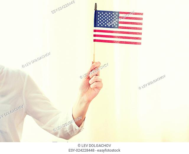 independence day, celebration, patriotism and holidays concept - close up of woman holding american flag in hand at 4th july party