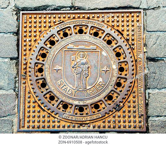 TRIER, GERMANY - 22 FEV 2015: Detail shot of Trier - Treves manhole cover on cobblestone pavement featuring the iconic city logo - MOnk with Bible and Kay