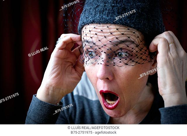 Middle-aged woman with veil in front of eyes, with the face of terror and open mouth