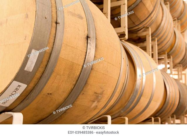 Rows of stacked wine barrels in wine cave