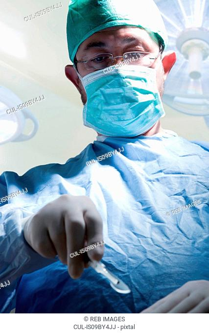 Surgeon with scalpel in operating theatre