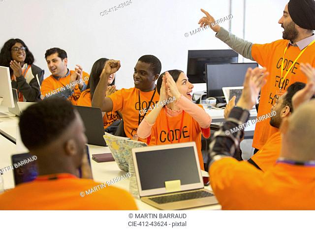 Happy hackers cheering and celebrating, coding for charity at hackathon
