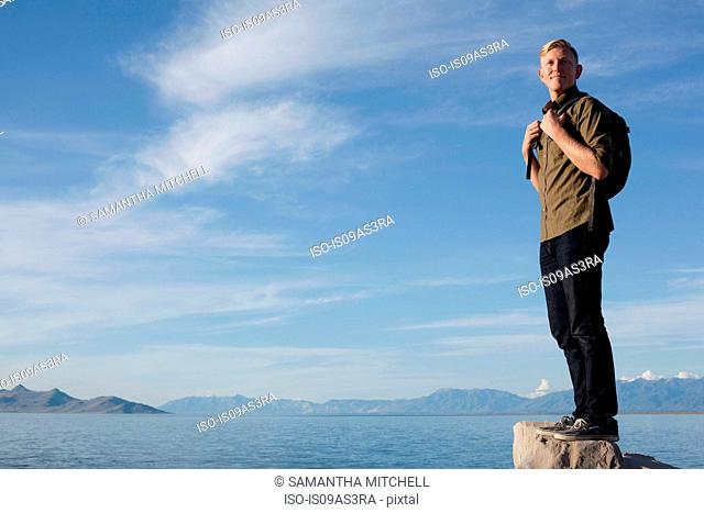Young man wearing backpack standing on rock looking away, Great Salt Lake, Utah, USA