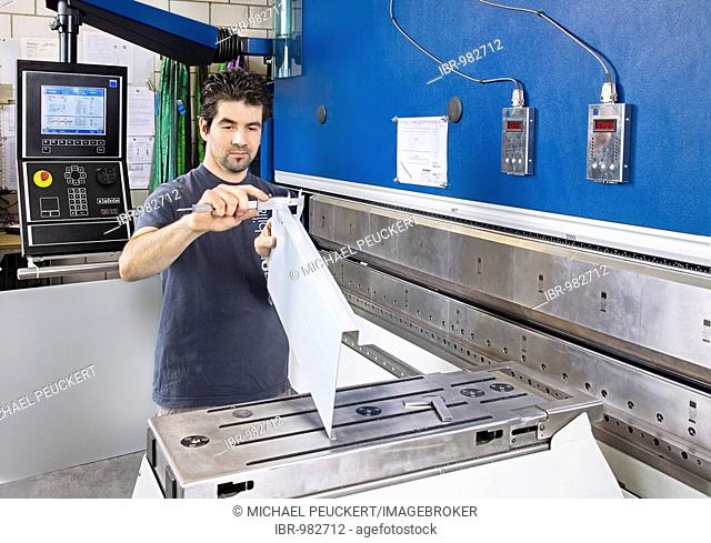 Employee of the locksmith's shop of the exhibition stand company Expomobilia installing and measuring metal bars at the bending press, Zurich, Switzerland