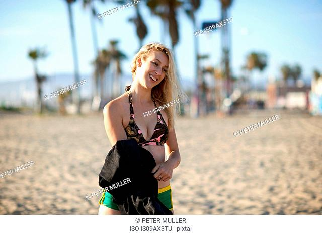 Young female surfer holding wetsuit on Venice Beach, California, USA