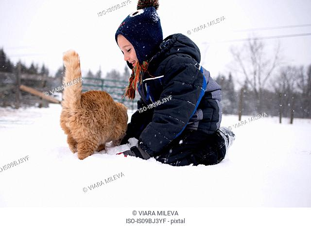 Boy playing with cat in snow