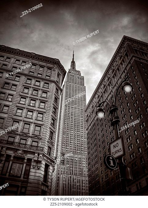 Empire state building between two buildings and lamp post