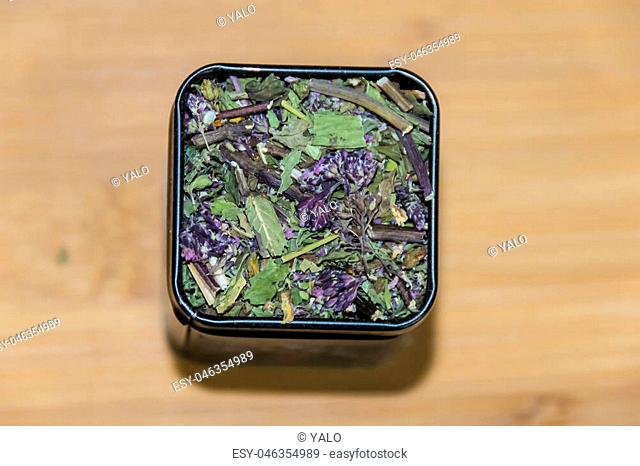 packing with dry green herbal tea on wooden background
