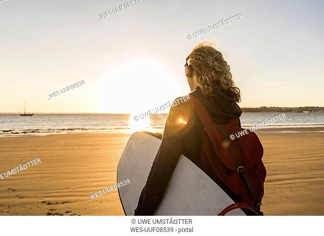 Teenage girl on the beach carrying surfboard