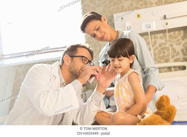 Male doctor using otoscope in ear of girl patient in hospital room