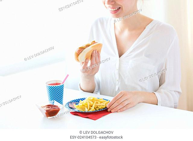 national holidays, celebration, food and patriotism concept - close up of happy woman eating hot dog and french fries with drink in paper cup at 4th july at...
