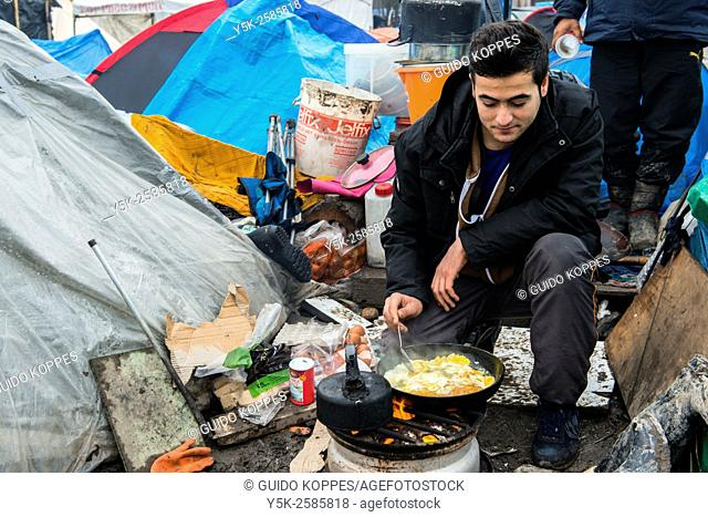 Dunkerque, France. Illegal migrant living in The Jungle of Dunkerque, cooking his breakfast of scambled eggs on a makeshift camp fire