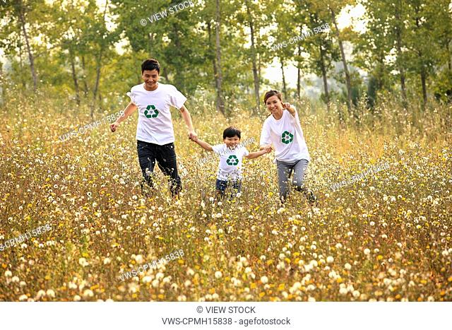 Young couple and son wearing recycle t-shirts running,Young couple and son wearing recycle t-shirts running,Contemporary