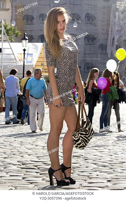 Beautiful, sexy and thin Ukrainian woman in a dress with leopard skin print posing for a photographic sequence in the ancient city of Lviv, Ukraine