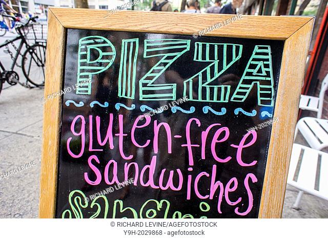 A sign outside of a restaurant in New York promotes their pizza and gluten-free sandwich offerings