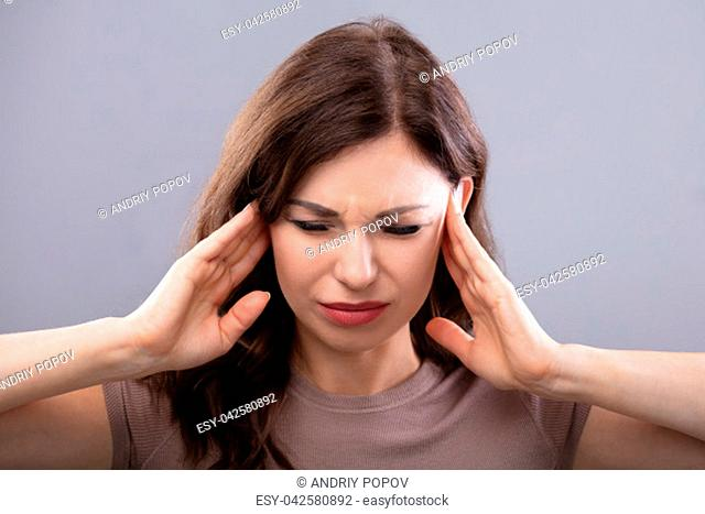 Young Woman Suffering From Headache On Grey Background