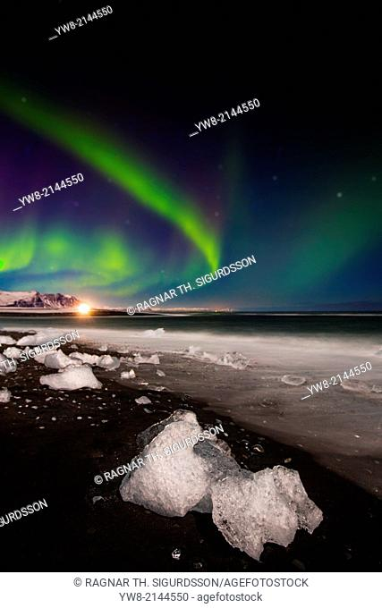 Aurora Borealis with icebergs on black sand beach, Iceland