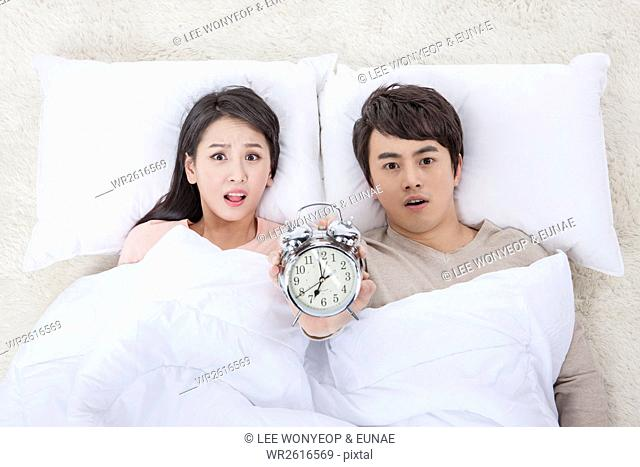 Young couple with alarm clock frowning faces