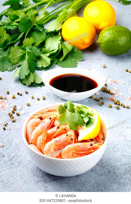 Seafood. Shrimps prawns with lemon, cilantro on a white plate. Selective focus