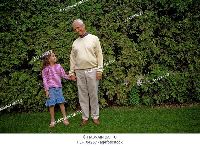 Smiling Grandfather and Granddaughter in Garden