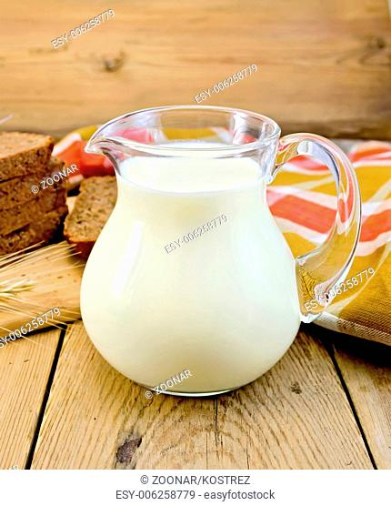 Milk in a jug with rye bread and red napkin