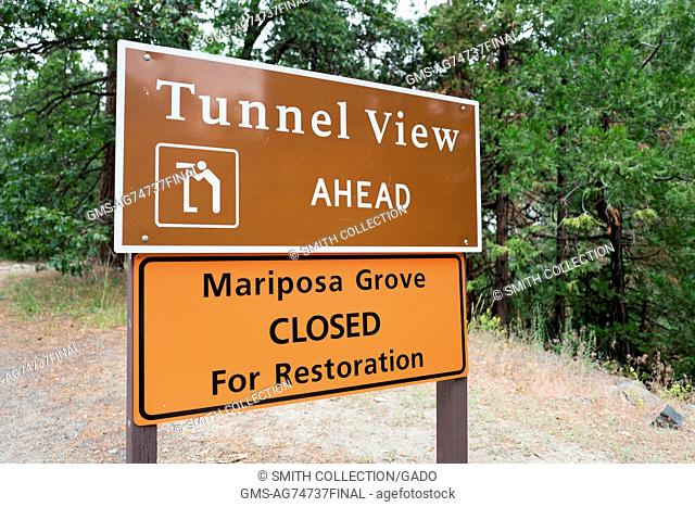 Sign for Tunnel View overlook in Yosemite National Park, with temporary sign announcing that the Mariposa Grove of giant sequoia redwood trees is closed