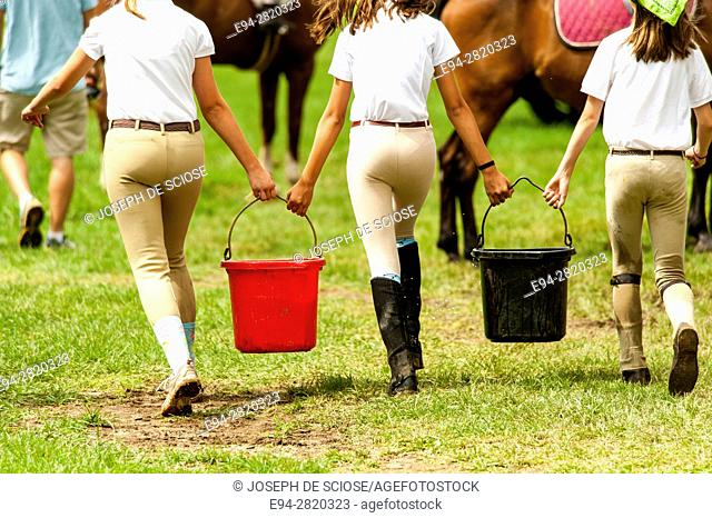 Back view of 3 teenage girls carrying buckets of water for horses and a horse riding competition
