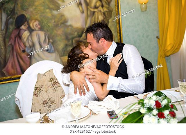 Bride and groom kissing ina restaurant