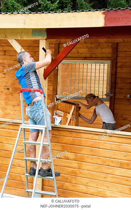 man and woman painting wooden building