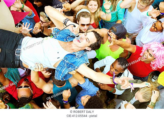 Performer with microphone crowd surfing at music festival