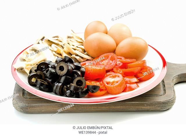 ingredients to make a mushroom omelette tomatoes and olives