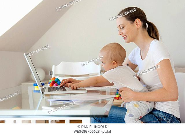 Smiling mother and little daughter using laptop together at table at home