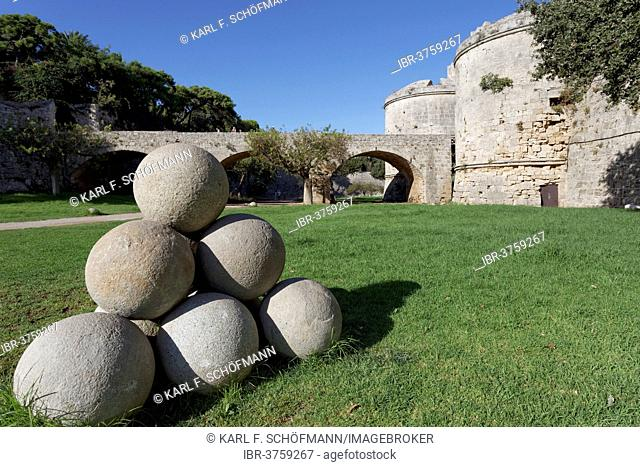 Cannonballs made of stone in the moat, d'Amboise Gate at back, medieval fortress, City of Rhodes, Island of Rhodes, Dodecanese Islands, Greece