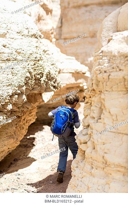 Caucasian boy exploring desert rock formations