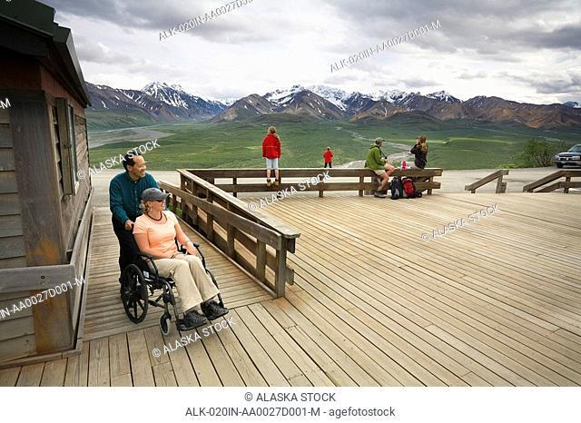 Adult man pushes a female in a wheelchair up a ramp at a handicap viewpoint PolyChrome Pass Denali National Park Alaska