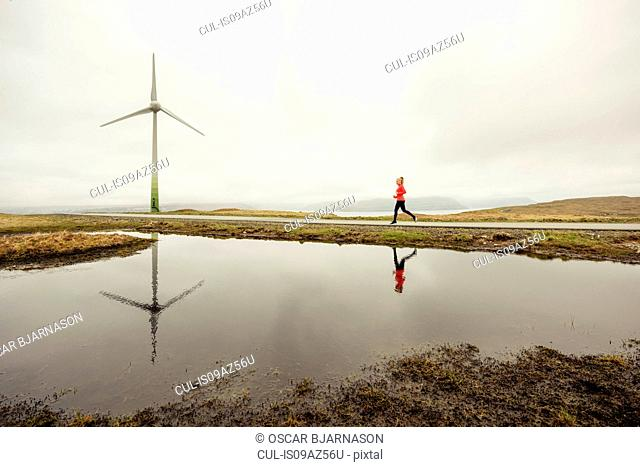Runner jogging on wind farm, Eysturoy, Faroe Islands