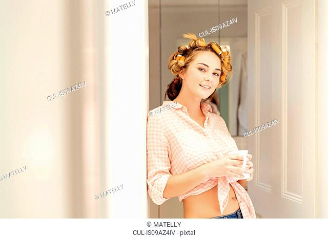 Portrait of young woman, foam rollers in hair, holding coffee cup