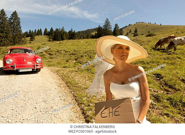 Bride waiting wayside of a pasture while groom sitting in his red vintage car