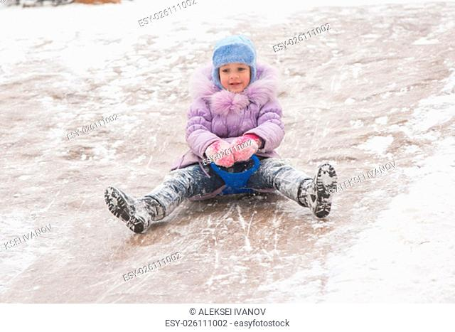 Five-year girl riding winter on a snowy hill surrounded by other children