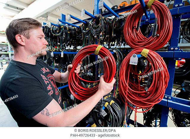 An employee of Satis & Fy sorts cables in the company warehouse in Karben, Germany, 23 June 2014. Business is booming for the event technology