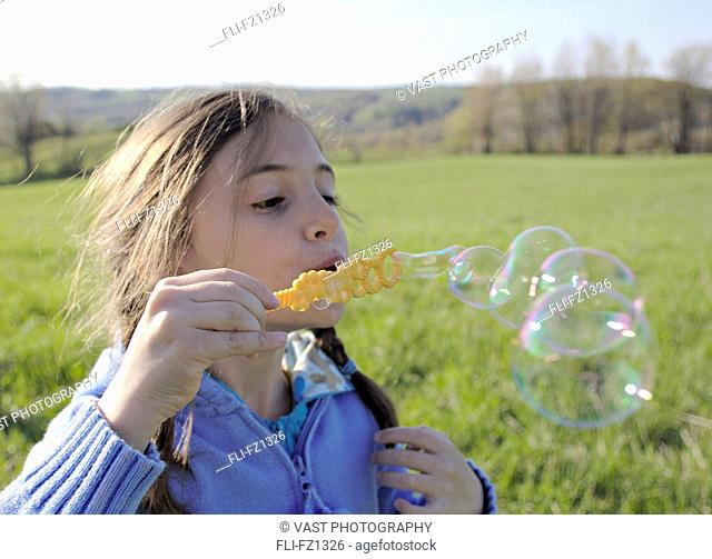 Artist's Choice: Girl in field blowing bubbles, Stayner, Ontario
