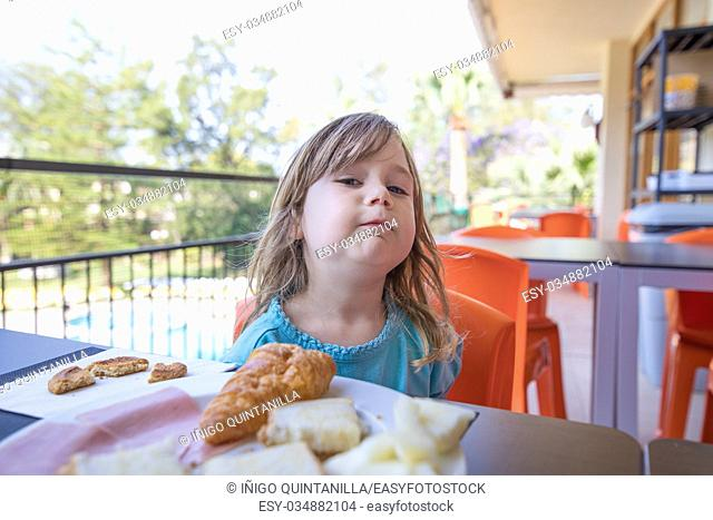 portrait of blonde caucasian child three years old with blue shirt, at breakfast, looking with challenging funny face, with food on dish