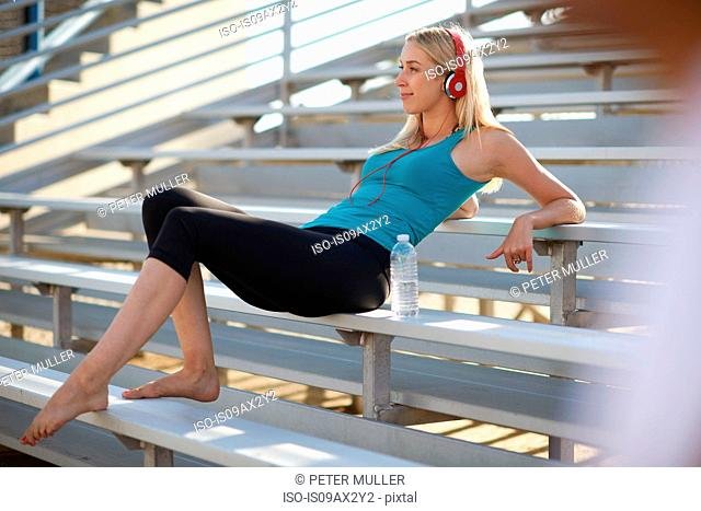 Young woman taking a break from exercise, sitting on bench seating, wearing headphones