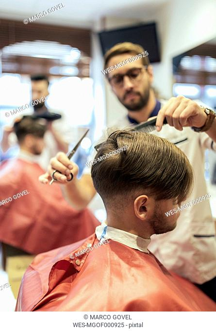 Barber cutting hair of a customer with twin brother in background
