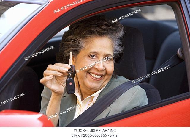 Senior Hispanic woman in car holding car keys