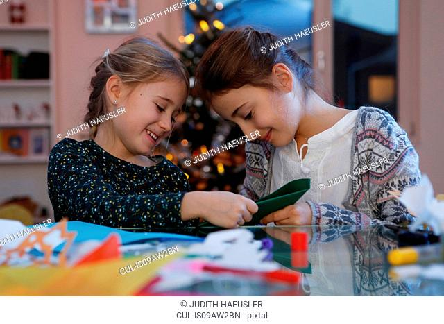 Girls at table doing christmas paper craft smiling