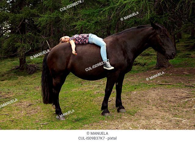 Girl lying bareback on horse in forest glade, Sattelbergalm, Tyrol, Austria