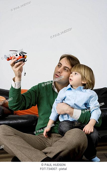 A father and son playing with a toy helicopter
