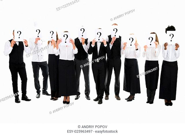 Full length of restaurant staff hiding faces with question mark signs against white background