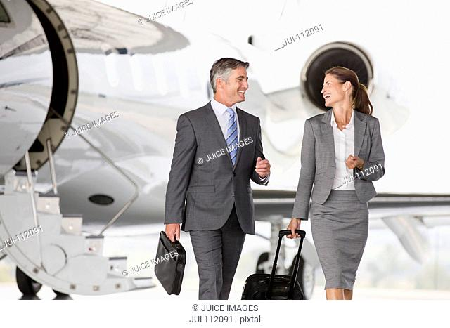 Smiling Businesswoman and Businessman leaving private jet